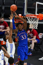 Kansas' David McCormack (33) is fouled by Kentucky's Cam'Ron Fletcher (21) during the second half of an NCAA college basketball game Tuesday, Dec. 1, 2020, in Indianapolis. (AP Photo/Darron Cummings)