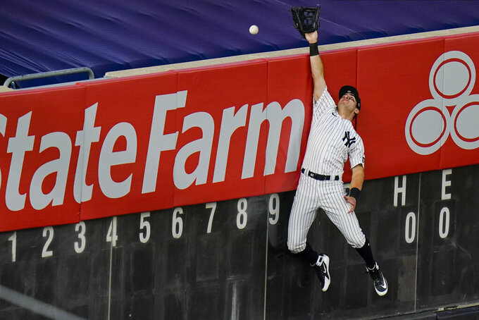 New York Yankees' Mike Tauchman (39) can't make the catch at the wall on a solo home run hit by Boston Red Sox's Xander Bogaerts during the third inning of a baseball game Saturday, Aug. 15, 2020, in New York. (AP Photo/Frank Franklin II)