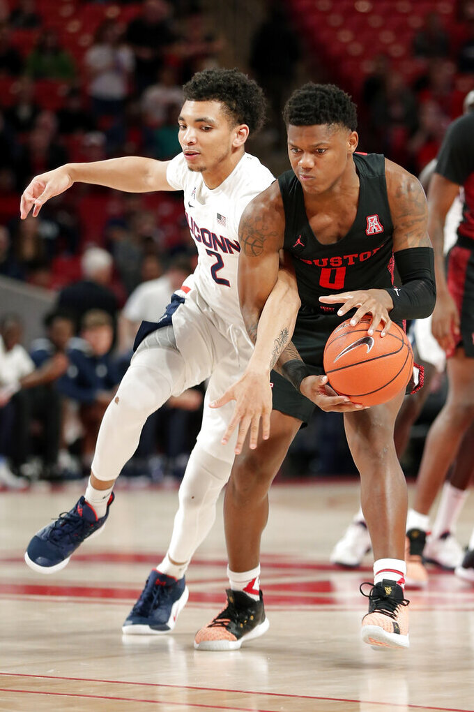 Connecticut guard James Bouknight (2) and Houston guard Marcus Sasser (0) tangle up as they battle for the ball on the tipoff during the first half of an NCAA college basketball game Thursday, Jan. 23, 2020, in Houston. (AP Photo/Michael Wyke)