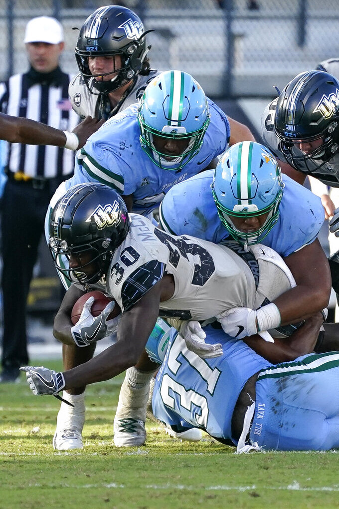 Central Florida running back Greg McCrae (30) is stopped by the Tulane defense including Tulane safety Macon Clark (37) during the second half of an NCAA college football game, Saturday, Oct. 24, 2020, in Orlando, Fla. (AP Photo/John Raoux)