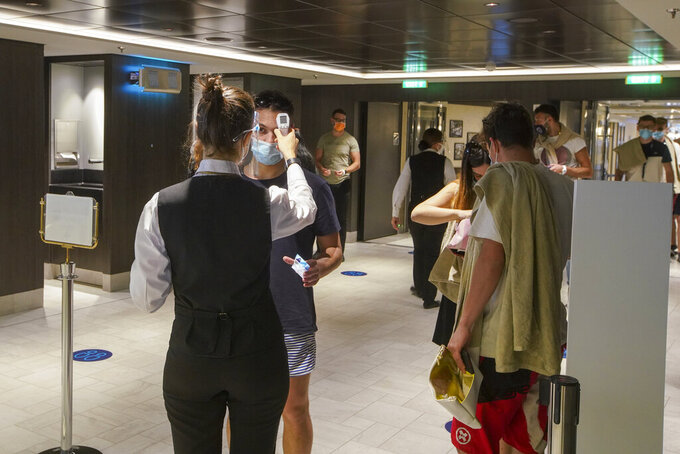 Passengers have their body temperature measured as they enter a restaurant of the MSC Grandiosa cruise ship in Civitavecchia, near Rome, Wednesday, March 31, 2021. MSC Grandiosa, the world's only cruise ship to be operating at the moment, left from Genoa on March 30 and stopped in Civitavecchia near Rome to pick up more passengers and then sail toward Naples, Cagliari, and Malta to be back in Genoa on April 6. For most of the winter, the MSC Grandiosa has been a lonely flag-bearer of the global cruise industry stalled by the pandemic, plying the Mediterranean Sea with seven-night cruises along Italy's western coast, its major islands and a stop in Malta. (AP Photo/Andrew Medichini)