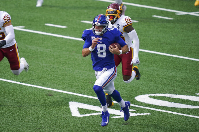 New York Giants' Daniel Jones (8) runs away from Washington Football Team's Landon Collins (26) during the first half of an NFL football game Sunday, Oct. 18, 2020, in East Rutherford, N.J. (AP Photo/John Minchillo)
