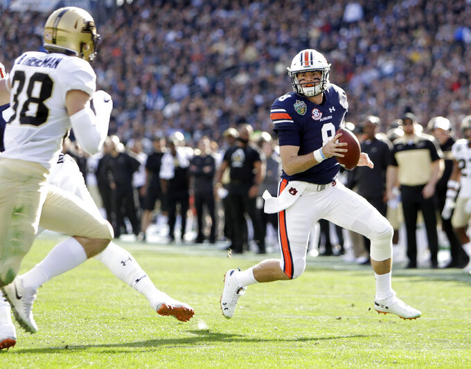 Auburn quarterback Jarrett Stidham (8) scrambles from Purdue safety Brennan Thieneman (38) in the first half of the Music City Bowl NCAA college football game Friday, Dec. 28, 2018, in Nashville, Tenn. (AP Photo/Mark Humphrey)