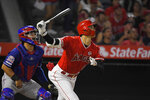 Los Angeles Angels' Shohei Ohtani flies out next to Texas Rangers catcher Jose Trevino during the fourth inning of a baseball game Wednesday, Aug. 28, 2019, in Anaheim, Calif. (AP Photo/Mark J. Terrill)