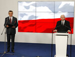 Marek Kuchcinski, left,the speaker of the Polish parliament, announces his resignation at a news conferencein Warsaw, Poland, Thursday, Aug. 8, 2019. His resignation was sparked by a scandal erupted over his and his family's frequent use of government planes. Kuchcinski insisted that he had done nothing wrong and had simply flown a lot in order to meet the residents of small towns far from the capital. But he said that