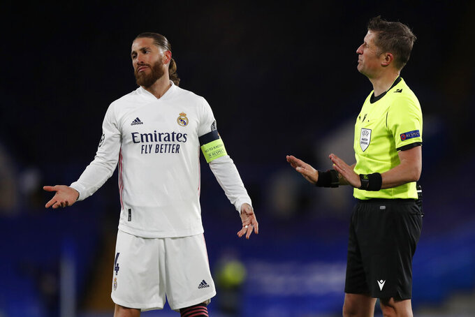 Real Madrid's Sergio Ramos gestures with Italian referee Daniele Orsato during the Champions League semifinal 2nd leg soccer match between Chelsea and Real Madrid at Stamford Bridge in London, Wednesday, May 5, 2021. (AP Photo/Alastair Grant)