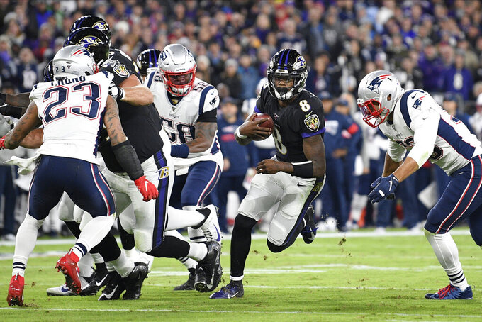 Baltimore Ravens quarterback Lamar Jackson (8) runs with the ball against the New England Patriots during the first half of an NFL football game, Sunday, Nov. 3, 2019, in Baltimore. (AP Photo/Nick Wass)