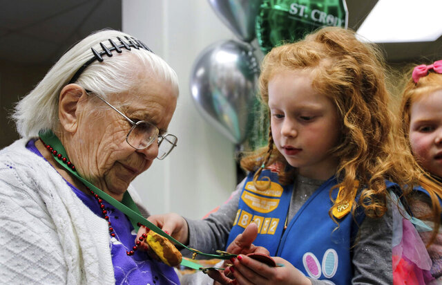 Abby Aitkin, right, a five-year-old Daisy Girl Scout, examines the awards given to Marian Seabold, 102, at a gathering in White Bear Lake, Minn. on Saturday, Feb. 15, 2020. The Girl Scouts were there to honor Seabold with a Lifetime Achievement award for her 65 plus years of service with the Girl Scouts. Seabold, who turns 103 on March 14, joined the Girl Scouts when she was 10, returning to lead when her daughter attended, then again when her granddaughter joined. (Deanna Weniger/Pioneer Press via AP)