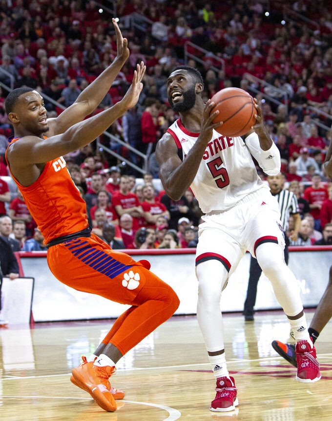 North Carolina State's Eric Lockett (5) drives against Clemson's Aamir Simms, left, during the first half of an NCAA college basketball game in Raleigh, N.C., Saturday, Jan. 26, 2019. (AP Photo/Ben McKeown)