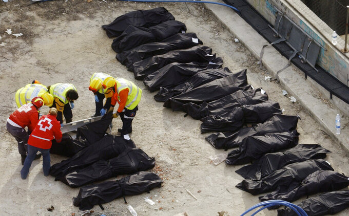 FILE - In this Thursday, March 11, 2004 file photo, rescue workers line up bodies beside a bomb-damaged passenger train at Atocha station following a series of explosions on trains in Madrid. (AP Photo/Denis Doyle)