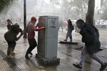 Demonstrators run for cover from a police water cannon during a protest in Santiago, Chile, Saturday, Oct. 19, 2019. The protests started on Friday afternoon when high school students flooded subway stations, jumping turnstiles, dodging fares and vandalizing stations as part of protests against a fare hike, but by nightfall had extended throughout Santiago with students setting up barricades and fires at the entrances to subway stations, forcing President Sebastian Pinera to announce a state of emergency and deploy the armed forces into the streets. (AP Photo/Esteban Felix)