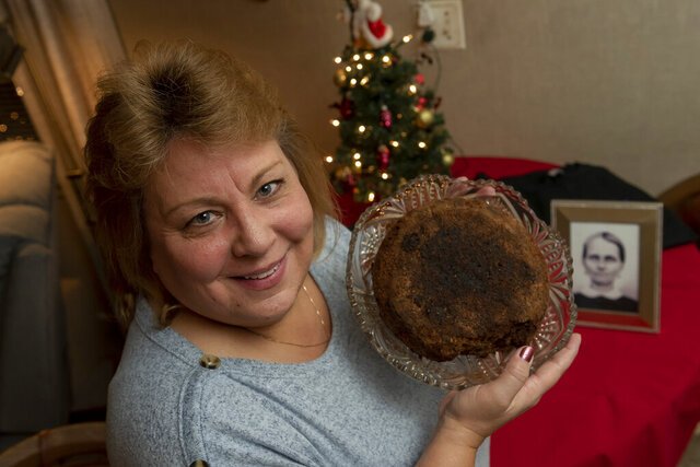 In this Dec. 9, 2019, photo Julie Ruttinger, of Tecumseh, Mich., holds a 141-year-old fruitcake, a family heirloom baked by her great-great-grandmother, Fidelia Ford, in 1878. Fidelia, pictured at left, died before the cake was served and the family, out of respect of her memory, decided not to eat it and has instead passed it down for generations. It resides in a glass case with the date of its creation affixed to the top. (David Guralnick/Detroit News via AP)