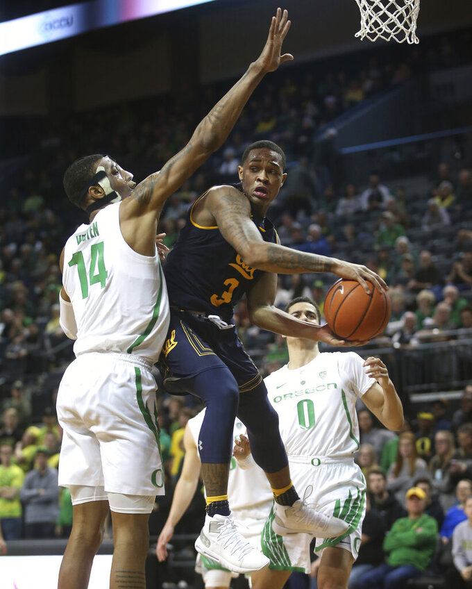 California's Paris Austin, center, passes the ball out under pressure from Oregon's Kenny Wooten, left, and Will Richardson, right, during the second half of an NCAA college basketball game Wednesday, Feb. 6, 2019, in Eugene, Ore. (AP Photo/Chris Pietsch)