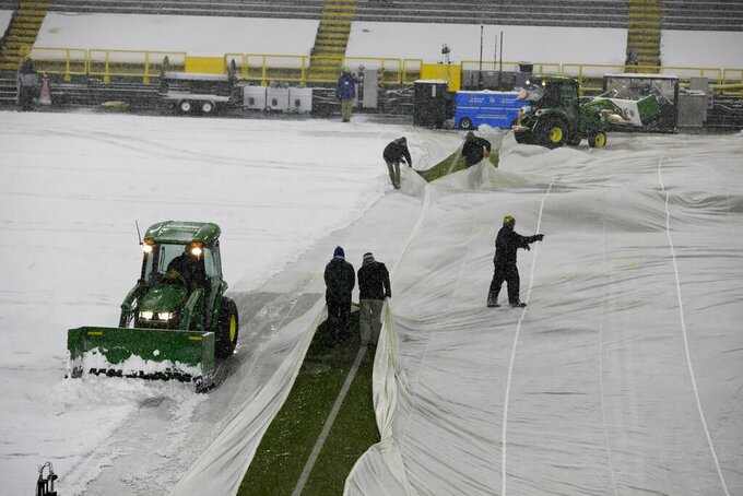 Workers get the field at Lambeau Field ready as it snows before an NFL football game between the Green Bay Packers and the Tennessee Titans Sunday, Dec. 27, 2020, in Green Bay, Wis. (AP Photo/Mike Roemer)