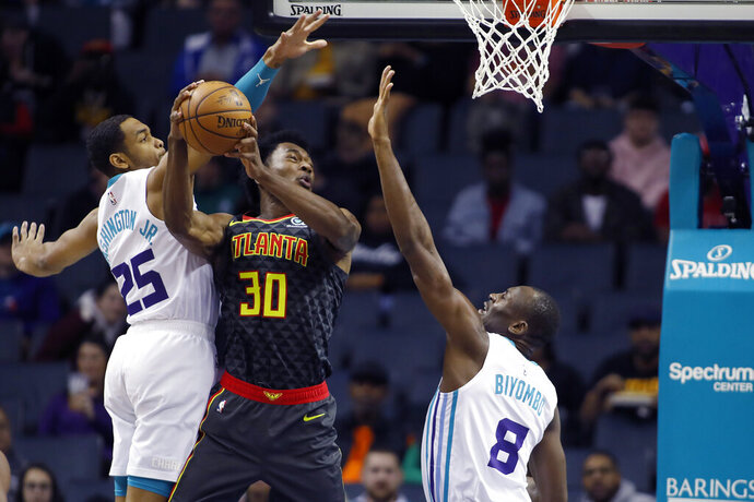 Atlanta Hawks' Damian Jones (30) tries to score as his shot is rejected by Charlotte Hornets' P.J. Washington (25) and Bismack Biyombo (8) during the first half of an NBA basketball game in Charlotte, N.C., Sunday, Dec. 8, 2019. (AP Photo/Bob Leverone)