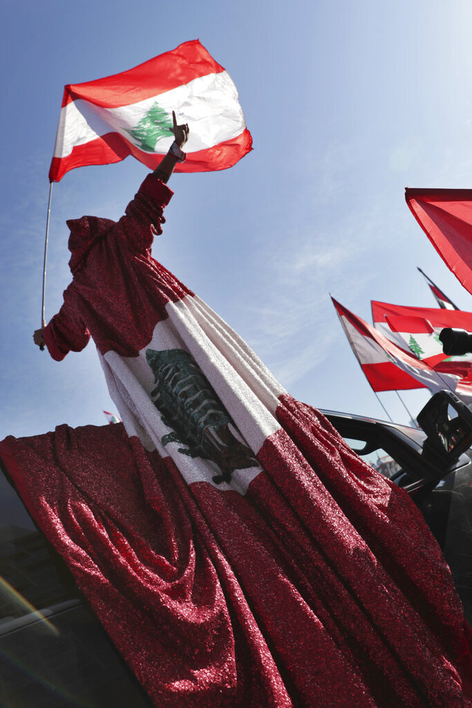 An anti-government protester wears a robe presenting the Lebanese national flag during an alternative independence celebrations at the Martyr square, in downtown Beirut, Lebanon, Friday, Nov. 22, 2019. Protesters gathered for their own alternative independence celebrations, converging by early afternoon on Martyrs' square in central Beirut, which used to be the traditional location for the official parade. Protesters have occupied the area, closing it off to traffic since mid-October. (AP Photo/Hassan Ammar)