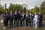 Ukrainian President Volodymyr Zelenskiy, centre, poses for photo with other officials as he visits the abandoned city of Prypyat some 3 kilometers (1.86 miles) from Chernobyl in Prypyat, Ukraine, Wednesday, July 10, 2019. A structure built to confine radioactive dust from the nuclear reactor at the centre of the 1986 Chernobyl disaster was formally unveiled on Wednesday.(Ukrainian Presidential Press Office via AP)