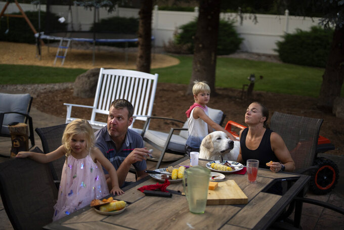 Melissa Stockwell has dinner with her husband, Brian Tolsma, and their children, Dallas and Millie, as they watch the Olympic games on the TV in their home in Colorado Springs, Colo., on Saturday, Aug. 7, 2021. (AP Photo/Emilio Morenatti)