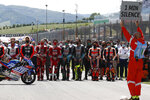 Teammates of 19 years-old Swiss pilot Jason Dupasquier and Moto3 pilots stand near his motorbike as they pay a minute of silence in his memory prior to the start of the Motogp Grand Prix of Italy at the Mugello circuit, in Scarperia, Italy, Sunday, May 30, 2021. Dupasquier died Sunday after being hospitalized Saturday, at the Florence hospital following his crash during the qualifying practices of the Moto3. (AP Photo/Antonio Calanni)