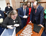 State Rep. Rocky Adkins, D-Sandy Hook, right, looks on as Melissa Bybee-Fields, Chief Clerk of the Kentucky House of Representatives, places canisters each containing the name of a house member into a bin at the Kentucky State Capitol in Frankfort, Ky., Tuesday, Jan. 8, 2019. The canisters containing the names are drawn to designate committee assignments. (AP Photo/Timothy D. Easley)
