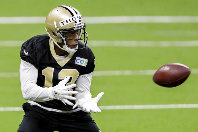 FILE - In this Saturday, Aug. 29, 2020, file photo, New Orleans Saints wide receiver Michael Thomas catches the ball during NFL football training camp in New Orleans. A person familiar with the situation says Sunday, Oct. 11, 2020, that Saints receiver Thomas has been suspended one game for conduct detrimental to the team after punching a teammate during practice. (David Grunfeld/The Advocate via AP, Pool, File)
