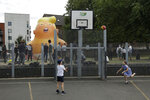 In this photo taken on Tuesday, July 10, 2018, children play basketball in the foreground as a six-meter high cartoon baby blimp of U.S. President Donald Trump stands inflated during a practice session in Bingfield Park, north London. Trump will get the red carpet treatment on his brief visit to England that begins Thursday: Military bands at a gala dinner, lunch with the prime minister at her country place, then tea with the queen at Windsor Castle before flying off to one of his golf clubs in Scotland. But trip planners may go out of their way to shield Trump from viewing another aspect of the greeting: an oversize balloon depicting the president as an angry baby in a diaper that will be flown from Parliament Square during what are expected to be massive gatherings of protesters opposed to Trump's presence. (AP Photo/Matt Dunham)