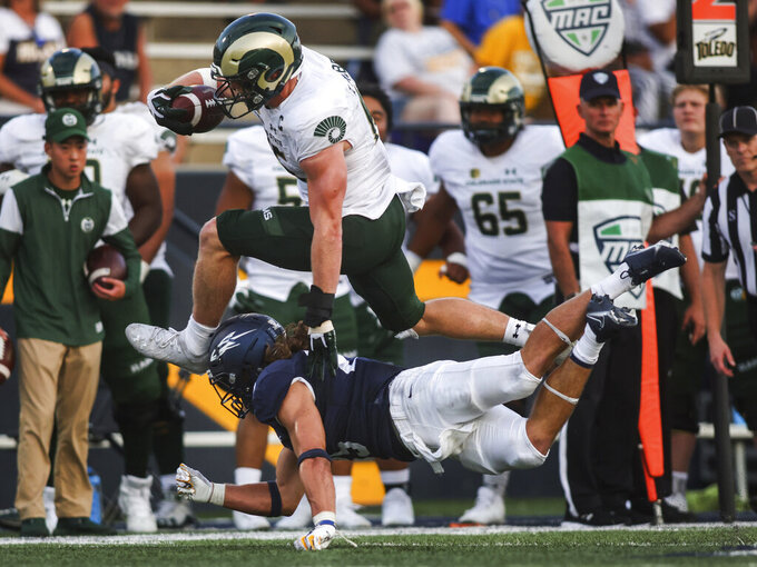 FILE - Colorado State's Trey McBride hurdles Toledo's Maxen Hook during an NCAA college football game in Toledo, Ohio, Saturday, Sept. 18, 2021. The player with the most receptions in college football midway through the first month is not a fleet-footed wide receiver with an NFL-bound quarterback. It's bruising Colorado State tight end McBride, who is drawing praise not only for his pass-catching, but also his blocking and leadership. (Rebecca Benson/The Blade via AP, File)