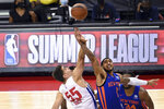 Detroit Pistons center Luka Garza (55) and New York Knicks forward Obi Toppin (1) reach for the ball on the opening tip of an NBA summer league basketball game Friday, Aug. 13, 2021, in Las Vegas. (AP Photo/David Becker)