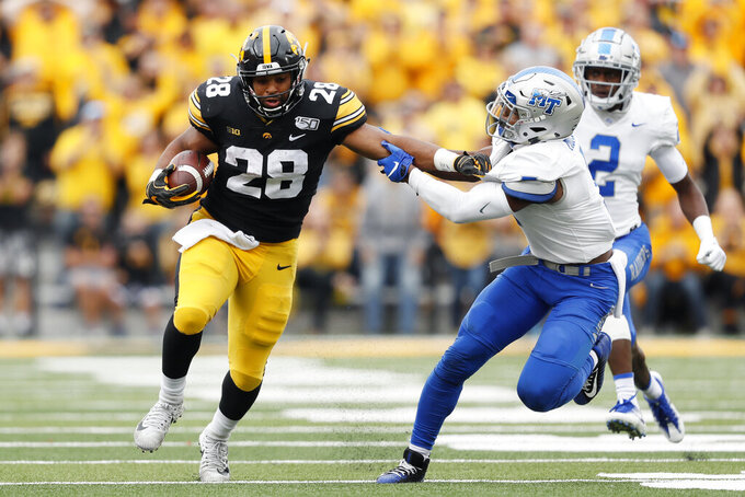 Iowa running back Toren Young (28) breaks a tackle by Middle Tennessee safety Jovante Moffatt, right, during the second half of an NCAA college football game, Saturday, Sept. 28, 2019, in Iowa City, Iowa. Iowa won 48-3. (AP Photo/Charlie Neibergall)