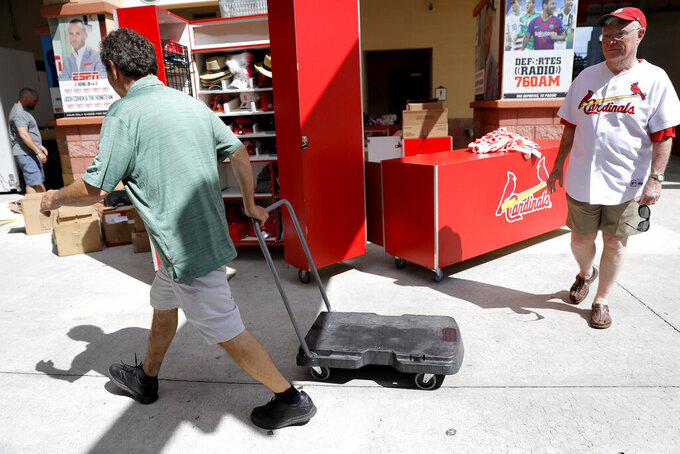 A St. Louis Cardinals fan, right, walks by as Roger Dean Stadium employees work on packing items, Friday, March 13, 2020, in Jupiter, Fla. Major League Baseball has delayed the start of its season by at least two weeks because of the coronavirus outbreak as well as suspended the rest of its spring training game schedule. (AP Photo/Julio Cortez)