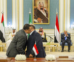 In this photo released by the Saudi Royal Palace, Yemeni Southern Transitional Council member and former Aden Governor Nasser al-Khabji, left, and Yemen's deputy Prime Minister Salem al-Khanbashi greet each other before signing a power-sharing deal witnessed by Yemen's president, Abed Rabbo Mansour Hadi, background right, Saudi Arabia's Crown Prince Mohammed bin Salman, center, and Dhabi's Crown Prince, Mohammed bin Zayed Al Nahyan, in Riyadh, Saudi Arabia, Tuesday, Nov. 5, 2019.  Yemen's internationally recognized government signed a power-sharing deal with Yemeni separatists that are backed by the United Arab Emirates. A picture of Saudi Arabia's founder late King Abdul Aziz Al Saud hangs on wall. (Bandar Aljaloud/Saudi Royal Palace via AP)