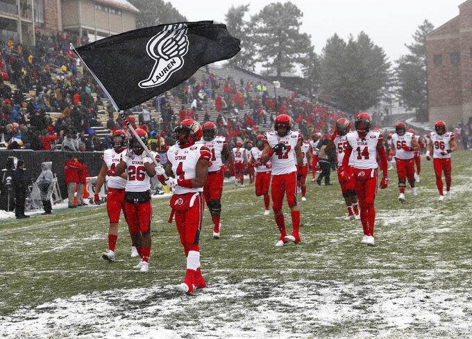 Utah running back TJ Green leads teammates on to the field to face Colorado in the first half of an NCAA college football game Saturday, Nov. 17, 2018, in Boulder, Colo. (AP Photo/David Zalubowski)