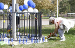 Cindy Toll places flowers at the Central Park memorial for the Saugus High School victims in Santa Clarita, Calif., Friday, Nov. 15, 2019. Investigators said Friday they have yet to find a diary, manifesto or note that would explain why a boy killed two students outside his Southern California high school on his 16th birthday. (AP Photo/Damian Dovarganes)