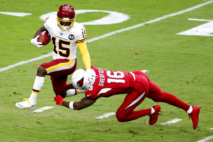Washington Football Team Steven Sims (15) tries to elude Arizona Cardinals Trent Sherfield (16) on a kick off return during the first half of an NFL football game, Sunday, Sept. 20, 2020, in Glendale, Ariz. (AP Photo/Darryl Webb)