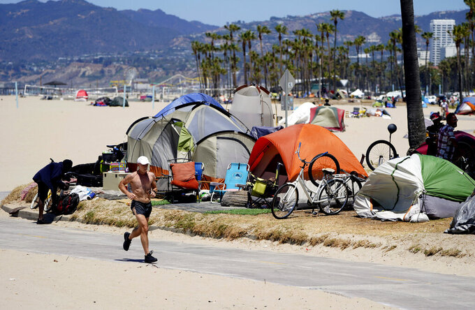 FILE - In this June 8, 2021, file photo, a jogger runs past a homeless encampment in the Venice Beach section of Los Angeles. California Gov. Newsom on Thursday, Sept 16, 2021, approved two measures to slice through local zoning ordinances as the most populous state struggles with soaring home prices, an affordable housing shortage and stubborn homelessness. Newson signed the most prominent legislation despite nearly 250 cities objecting that it will, by design, undermine local planning and control. (AP Photo/Marcio Jose Sanchez, File)