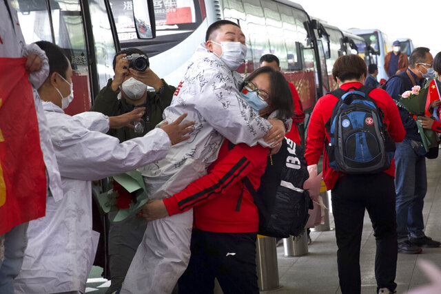 A medical worker from China's Jilin Province, in red, embraces a colleague from Wuhan as she prepares to return home at Wuhan Tianhe International Airport in Wuhan in central China's Hubei Province, Wednesday, April 8, 2020. Within hours of China lifting an 11-week lockdown on the central city of Wuhan early Wednesday, tens of thousands people had left the city by train and plane alone, according to local media reports. (AP Photo/Ng Han Guan)