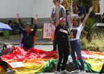 Gay rights activists protest outside of the Constitutional Court, waiting for the court's decision on gay marriage, in Quito, Ecuador, Tuesday, June 4, 2019. The court through a statement said that it has postponed its decision until a new session. (AP Photo/Dolores Ochoa)