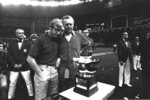 FILE - In this Dec. 23, 1974, file photo, North Carolina State coach Lou Holtz, left, and Houston coach Bill Yeoman look over the Astro-Bluebonnet Bowl trophy in Houston. The football teams played to a 31-31 tie, but Yeoman awarded the trophy to North Carolina State after the game. Yeoman, the longtime Houston football coach who led the Cougars to four Southwest Conference titles and a school-record 160 victories, has died. He was 92. The university announced the death Wednesday, Aug. 12, 2020, without providing details. Son, Bill Jr., told ESPN his father died of pneumonia and kidney failure. (AP Photo, File)