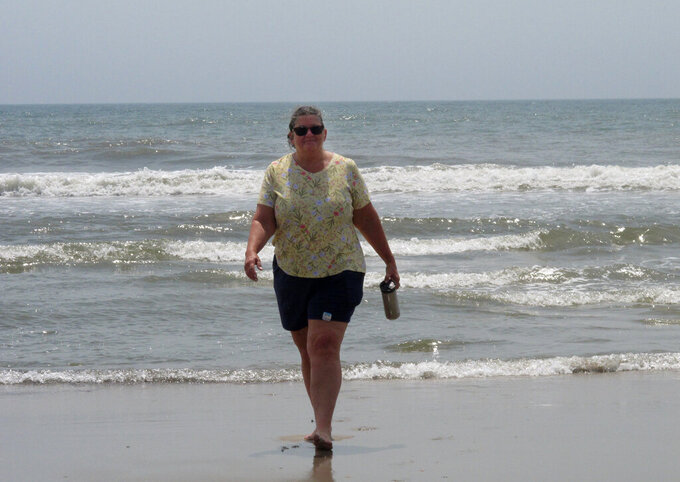Suzanne Hornick walks from the surf in Ocean City N.J. on July 8, 2021. She is a leader of a residents group that opposes three offshore wind energy projects approved for the ocean off Ocean City. (AP Photo/Wayne Parry)