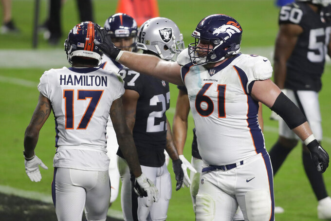 Denver Broncos offensive guard Graham Glasgow (61) reacts after wide receiver DaeSean Hamilton (17) scored a touchdown against the Las Vegas Raiders during the second half of an NFL football game, Sunday, Nov. 15, 2020, in Las Vegas. (AP Photo/Isaac Brekken)