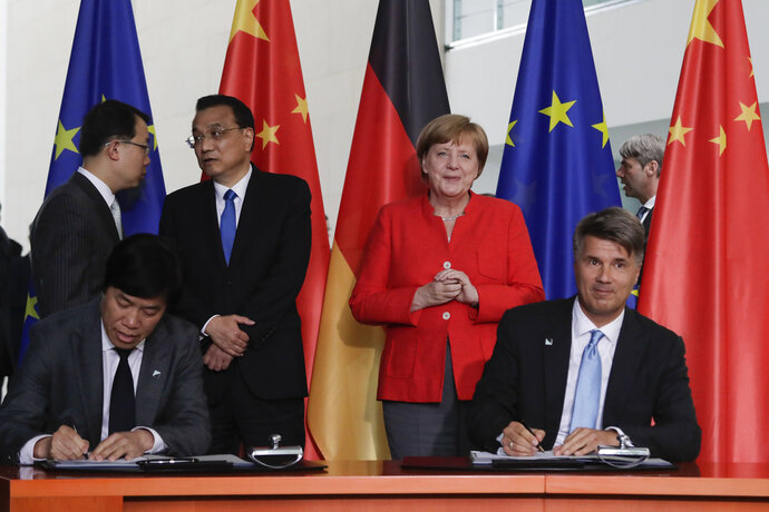 FILE - In this July 9, 2018 file photo German Chancellor Angela Merkel, second from right, and Chinese Premier Li Keqiang, third from left, attend a contracts signing ceremony between German car maker BMW CEO Harald Krueger, right, and Qi Yumin CEO of the Brilliance Group, left front, during a meeting in the chancellery in Berlin. German automaker BMW said Thursday, Oct. 11, 2018 it is taking a majority stake in its China joint venture and investing 3 billion euros in future production there as it prepares to meet increased demand for electric vehicles. (AP Photo/Markus Schreiber, file)