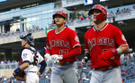 Los Angeles Angels Shohei Ohtani, center, of Japan, and Mike Trout, right, head to the dugout after Ohtani's two-run home run off Minnesota Twins pitcher Jose Berrios (not shown) in the third inning of a baseball game Monday, May 13, 2019, in Minneapolis. Twins catcher Jason Castro, left, looks on. (AP Photo/Jim Mone)