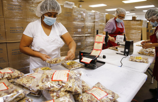 Rebecca Gonzales works on applying new stickers on bags of mixed nuts previously planned for Hawaiian flight service at GNS Foods in Arlington, Texas, Tuesday, July 28, 2020. GNS Foods is working on selling bags of nuts to customers through its retail store. Sales to airlines has dropped dramatically due to the stoppage of serving nuts during the COVID-19 pandemic. (Vernon Bryant/The Dallas Morning News via AP)