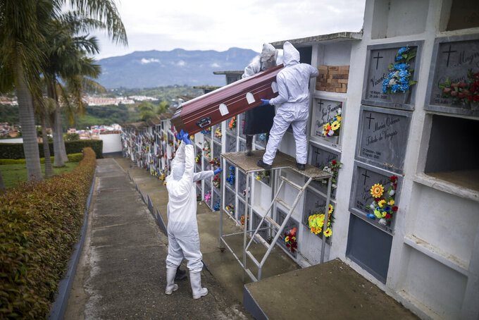 Cemetery and funeral workers place the coffin of a man who died of COVID-19 into a niche at the Nuestra Señora de Belen cemetery in Fusagasuga, Colombia, Wednesday, June 9, 2021. (AP Photo/Ivan Valencia)