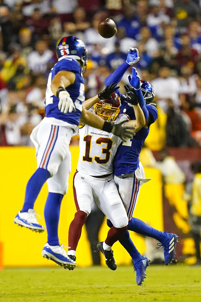 Washington Football Team wide receiver Adam Humphries (13) looses the ball as he is covered by New York Giants cornerback James Bradberry (24) and New York Giants inside linebacker Blake Martinez (54) during the second half of an NFL football game, Thursday, Sept. 16, 2021, in Landover, Md. (AP Photo/Patrick Semansky)