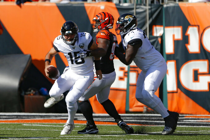 Jacksonville Jaguars quarterback Gardner Minshew (15) is sacked by Cincinnati Bengals defensive tackle Geno Atkins, center, in the first half of an NFL football game, Sunday, Oct. 20, 2019, in Cincinnati. (AP Photo/Gary Landers)