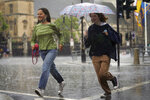 Two women run through Parliament Square in central London, Sunday July 25, 2021. Thunderstorms bringing lightning and torrential rain to the south are set to continue until Monday it is forecast. (Victoria Jones/PA via AP)