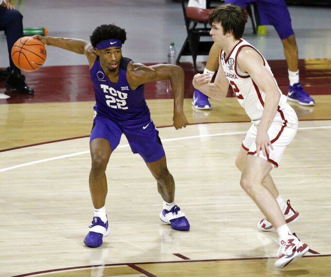 TCU's RJ Nembhard (22) goes against Oklahoma's Austin Reaves (12) during the first half of an NCAA college basketball game in Norman, Okla., Tuesday, Jan. 12, 2021. (AP Photo/Garett Fisbeck)