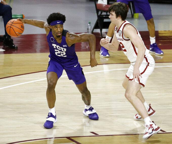 TCU's RJ Nembhard (22) goes against Oklahoma's Austin Reaves (12) during the first half of an NCAA college basketball game in Norman, Okla., Tuesday, Jan. 12, 2021. (AP Photo/Garett Fisbeck)