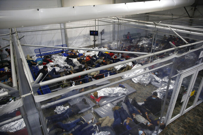 Minor children are housed inside a pod at the Donna Department of Homeland Security holding facility, the main detention center for unaccompanied children in the Rio Grande Valley run by U.S. Customs and Border Protection (CBP), in Donna, Texas, Tuesday, March 30, 2021. The minors are housed by the hundreds in eight pods that are about 3,200 square feet in size. Many of the pods had more than 500 children in them. The Biden administration on Tuesday for the first time allowed journalists inside its main detention facility at the border for migrant children, revealing a severely overcrowded tent structure where more than 4,000 kids and families were crammed into pods and the youngest kept in a large play pen with mats on the floor for sleeping.(AP Photo/Dario Lopez-Mills, Pool)
